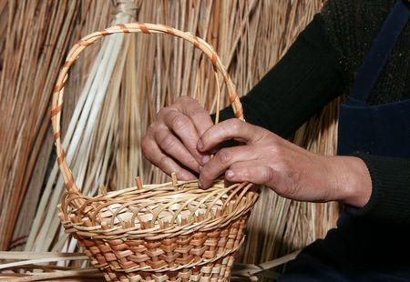 Female hands manually mastering woven wicker basket