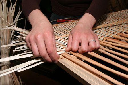 manually: Female hands manually mastering wicker fabric