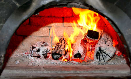 flaming wood in old home brick fireplace Stock Photo