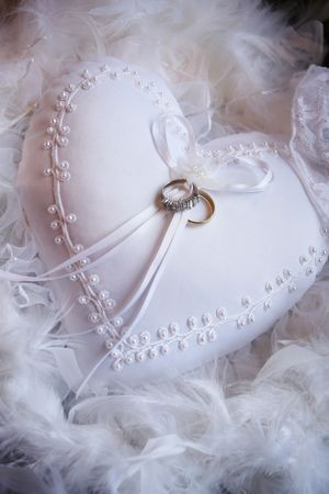 Wedding rings on a white textile heart photo