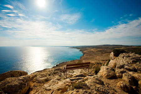 Wooden bench on the rock over sea in sunset light Stock Photo - 9568656