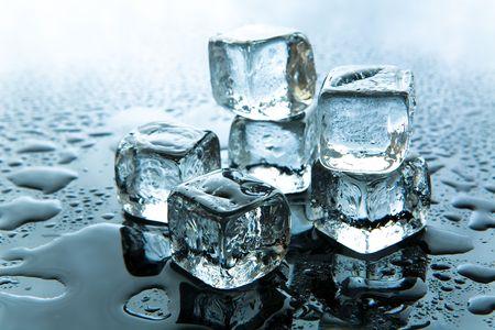 Melting ice cubes on reflective background