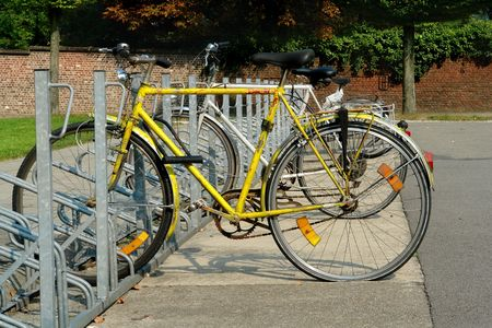 Bicycle rack or bike stand with old worn repainted rusted student bikes on campus, with a flat tire. Stock Photo