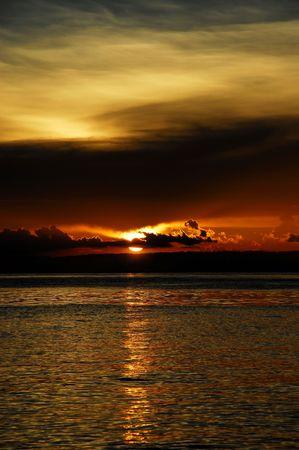flamboyant: Chocolade-koffie gekleurde flamboyante zonsondergang op een tropisch exotisch strand met gouden reflecties in de zee en de bergen op de achtergrond. Stockfoto