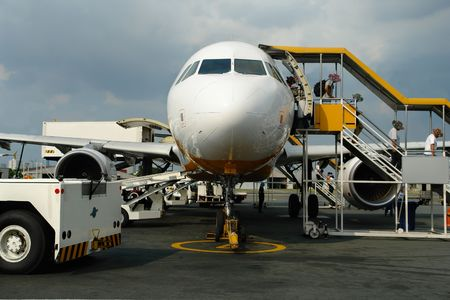 Passengers exiting commercial airliner by stairs on an airport. Stock Photo