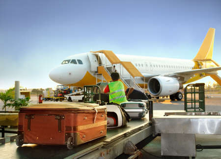 Luggage handling on airport: transfer from cart to the luggage carousel with airplane and cargo loading in the background and detail of suitcases. Stock Photo