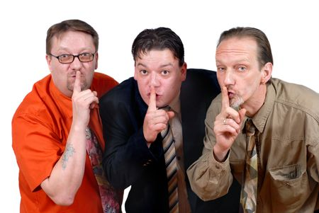 shush: Three slick punk-like alternative sales or business men embodying the concept of keeping discreet not to let competitors play in their cards. Asking for privacy and secrecy. Stock Photo