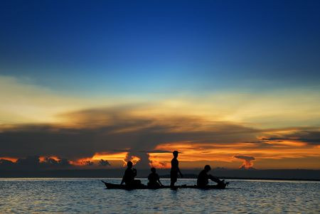 Asian childrens silhouette in a canoe at sea in front of a tropical flamboyant sunset. photo