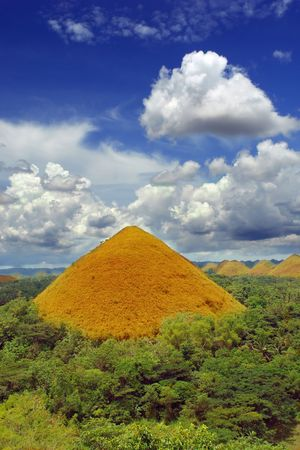 One Bohol Chocolate Hill, a natural landmark and a very prominent and famous tourism geography spot in the Philippines, colorful and under a majestic cloudscape. photo