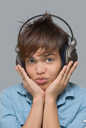Portrait of eighteen year Asian teen boy with headphones listening to music and holding his head while blowing mockingly. photo