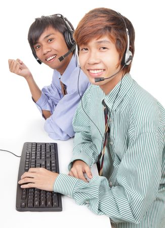 Two Asian call center agents or customer care representatives with headset and keyboard at work listening and smiling friendly radiating trust and professionalism. Isolated over white. photo