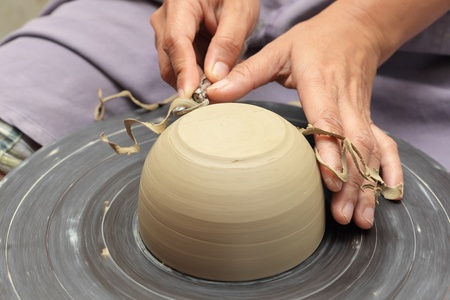 Potters hands milling clay bowl on a turning wheel with a carving tool in a pottery, scraping excess clay off in curls.