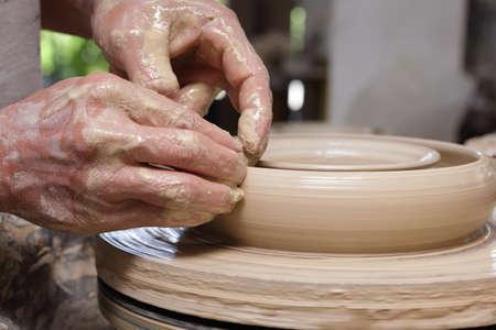 alfarero: Recorta el primer plano de manos de potter dando forma de arcilla en una rueda de inflexi�n en la placa de utensilios de cocina en una cer�mica de Filipinas asi�ticos.
