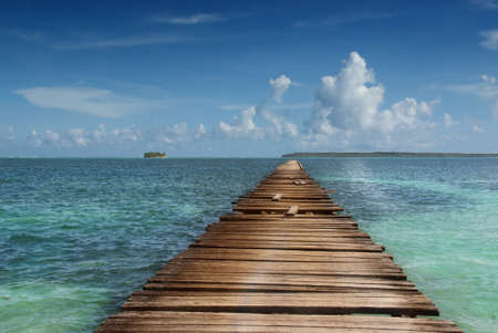 Wooden pier pointing to pristine island in tropical sea. Concept of simplicity, purpose, direction and infinity. Stock Photo