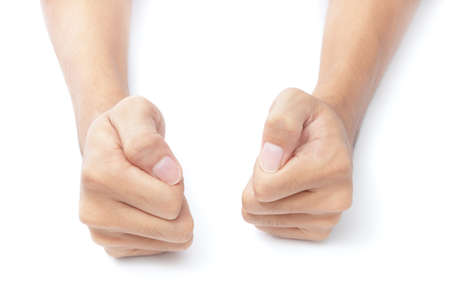 Too juxtaposed male hands on a white desktop making fists.