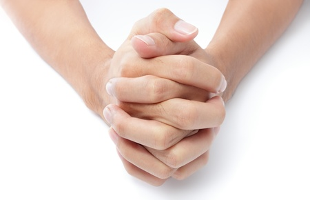 intertwined: Close-up frontal top view of two hands folded with intertwined fingers praying on a white desktop. Stock Photo