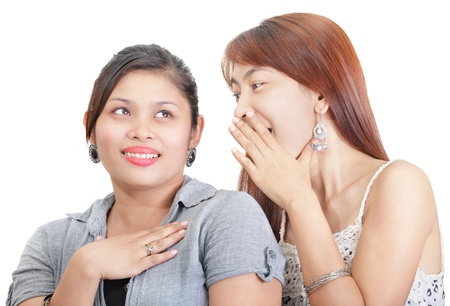 Close-up portrait of  two Asian college youth girls gossiping, telling secrets or spilling the beans privately. One Japanese-Chinese looking girl eagerly does the talking while the other Indian-looking girl listens smiling with her hand on her heart and l Stock Photo