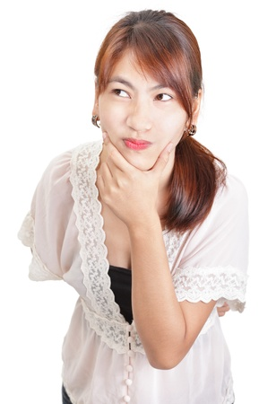 fishy: Portrait of a skeptical young and unapproachable Asian woman in chaste lace outfit holding a hand on her chin and looking fishy and doubtful. Isolated over white. Stock Photo