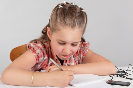 Portrait of young eager elementary school girl making homework assignment, intensively concentrated on her task, sticking out her tongue to emphasize her effort, focus and dedication to learn and solve a problem. photo