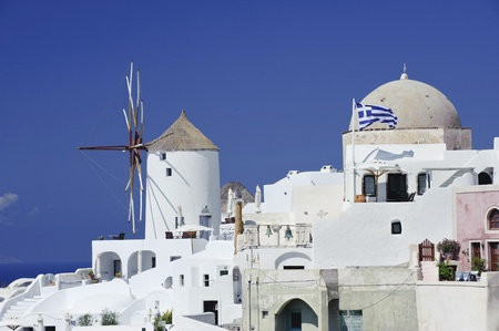 cupolas: Winmill in Oia town with flag of Greece on Santorini island, Greece