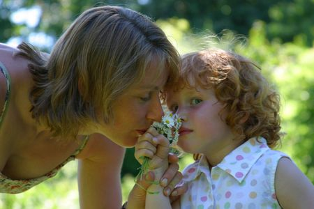 constitutionality: Mother and daughter smelling the daisies Stock Photo