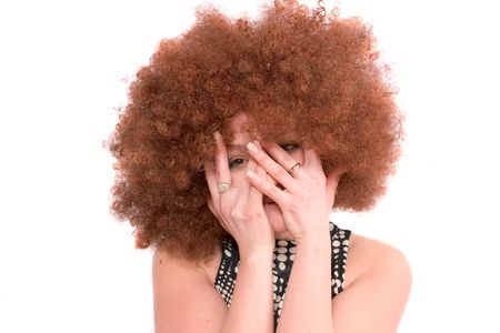 afro hairdo: Pretty girl with red afro wig hiding her face in her hands