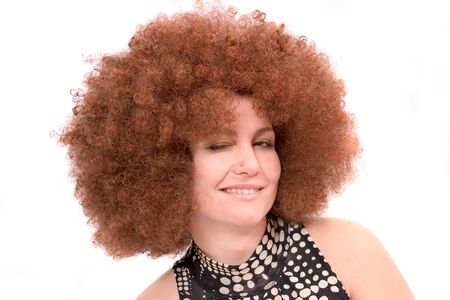winking: Pretty woman with red afro wig winking Stock Photo