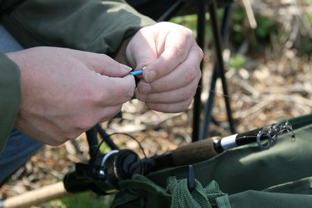 angling: Man working on preparing his angling gear for a fishing session