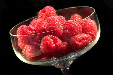 Bowl of fresh raspberries on black background photo