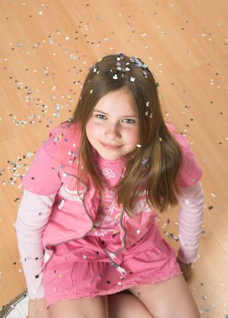 Little blond girl sitting on the floor covered in confetti Stock Photo - 396354