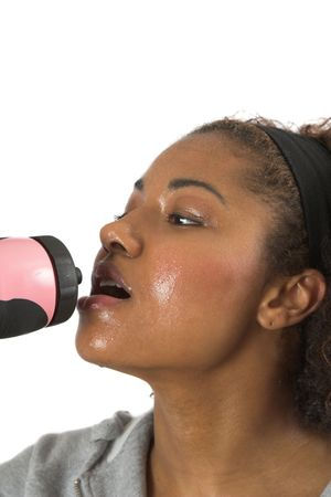 Woman with sweaty face having a refreshing drink after her workout Stock Photo