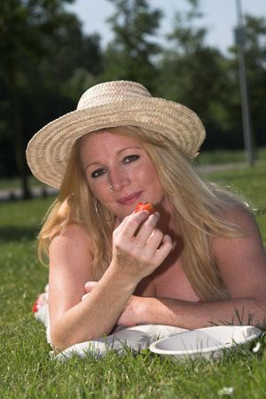 nosering: Beautiful blond woman relaxing and eating strawberries in the park