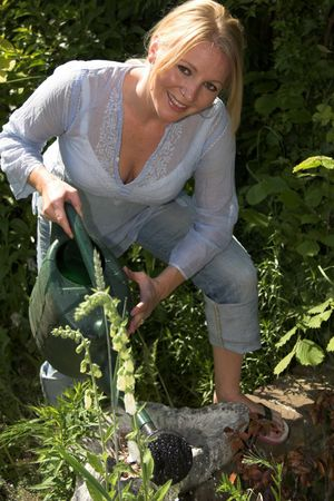 nosering: Blond woman watering the plants in the garden on a sunny day