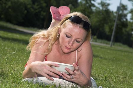 nosering: Pretty blond woman looking at her empty bowl lying on the grass