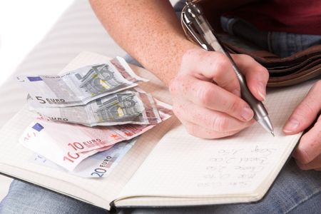 household money: Womanhand writing down the expenses paid while some euro bills are lying on her household book Stock Photo
