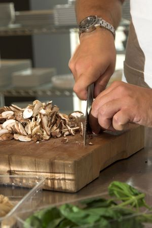 Italian chef working in the kitchen chopping up the champignons Stock Photo