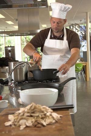 Italian chef stirring the food (shallow DOF, focus on chef)