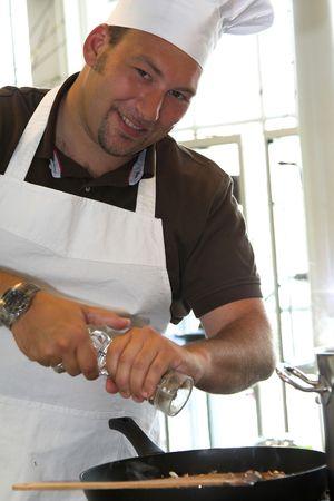 Italian chef adding some pepper to his pasta dish