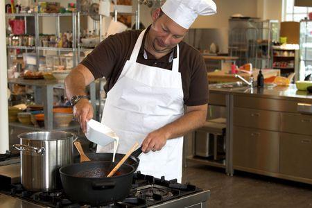 Italian chef adding some cream into the pasta sauce