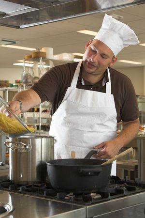 adding: Italian chef adding the pasta to the boiling water