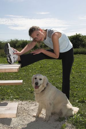 picknick: Pretty woman doing stretching exercises on a outdoor picknick bench while her dog is patiently waiting Stock Photo