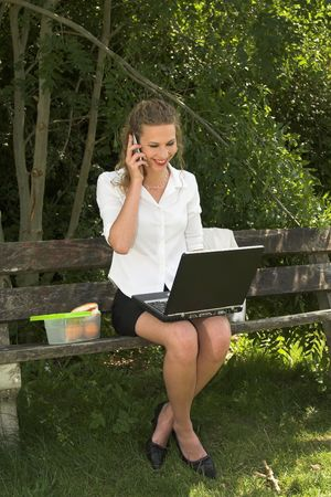 Pretty businesswoman talking on the phone in the park and looking very happy photo