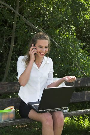 Pretty businesswoman outdoors in the park getting some good news by phone photo
