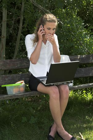 Pretty businesswoman sitting in the park having her lunchbreak while doing some work on her laptop and talking on the phone; looking shocked photo