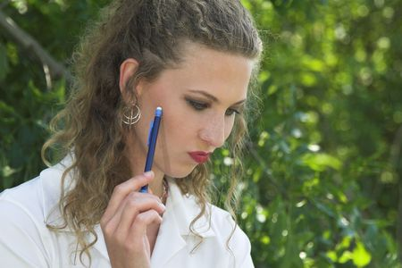 lunchbreak: pretty businesswoman with a pencil to her face thinking hard