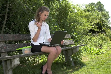Businesswoman in the park working on her laptop photo