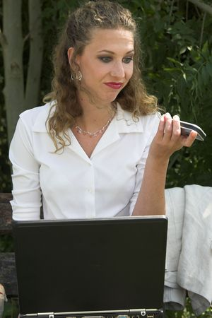 Pretty business woman pulling faces at her phone after just ending a conversation photo