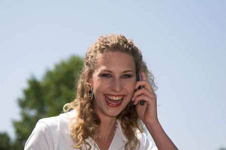 lunchbreak: Pretty businesswoman laughing while on the phone outdoors