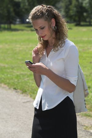 lunchbreak: Businesswoman enjoying her lunch break in the park and sending a text message on her mobile phone Stock Photo