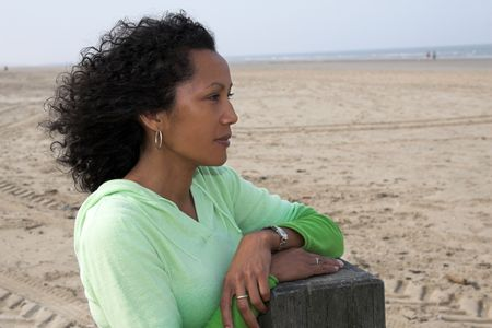 Beautiful black woman with the wind through her hair overlooking the sea Stock Photo - 458429